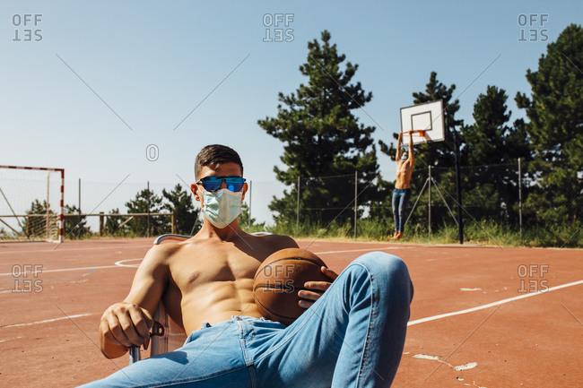 Young man relaxing on chair with man exercising in background at basketball court