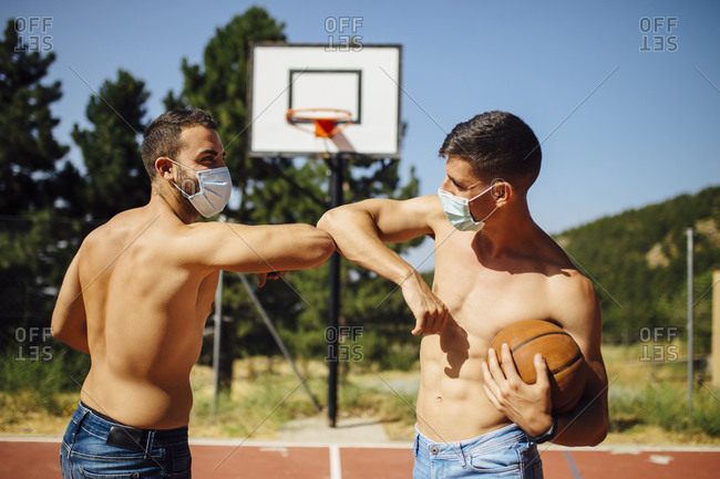 Athletes with face mask greeting with elbow bump at basketball court
