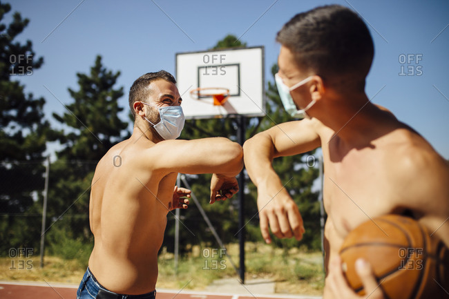Men with face mask greeting with elbow bump at basketball court