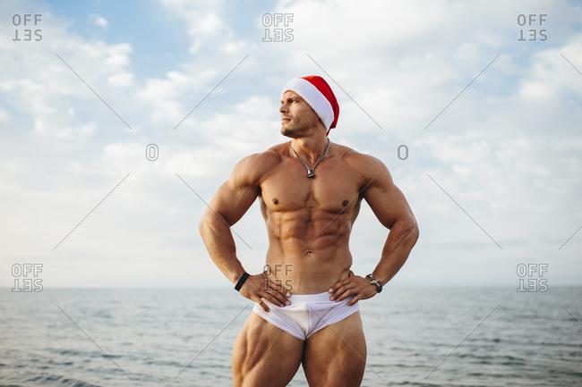 Shirtless macho man wearing Santa hat standing against sea