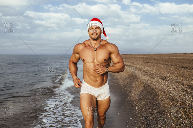 Smiling muscular young man wearing Santa hat running at beach against cloudy sky