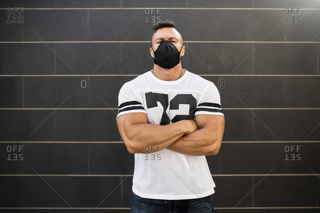 Macho young man wearing face mask standing against wall