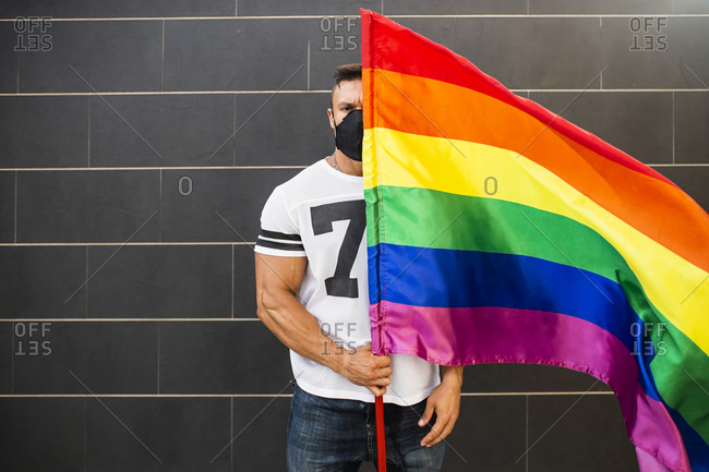 Young man wearing mask holding rainbow flag while standing against wall