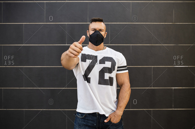 Macho man wearing face mask showing thumbs up while standing against wall