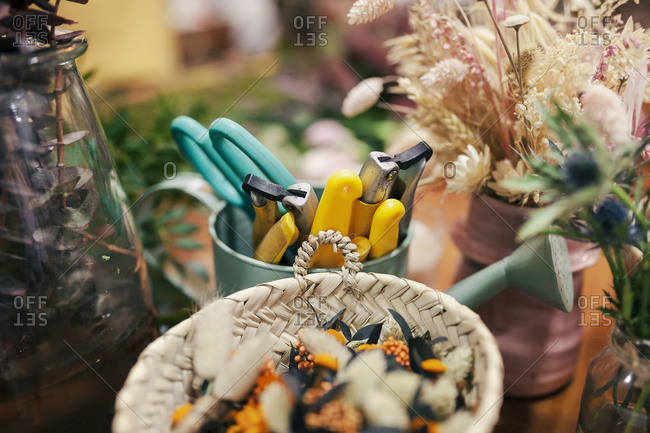 Gardening tool and flowers kept on table at flower shop