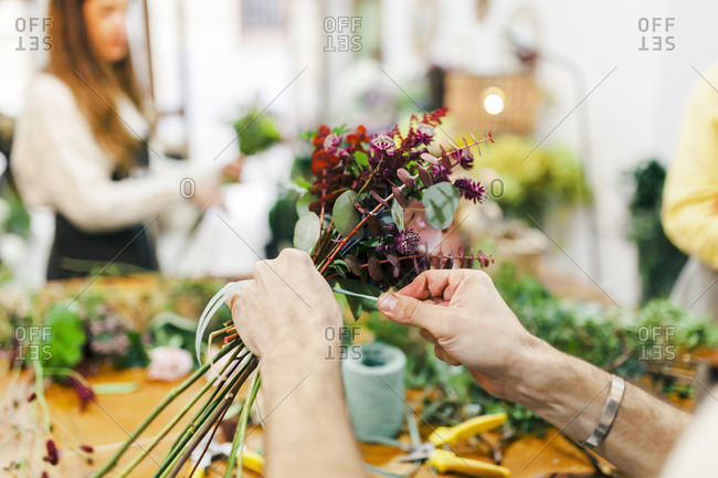 Florist hand tying bunch of flower with team working in background at flower shop