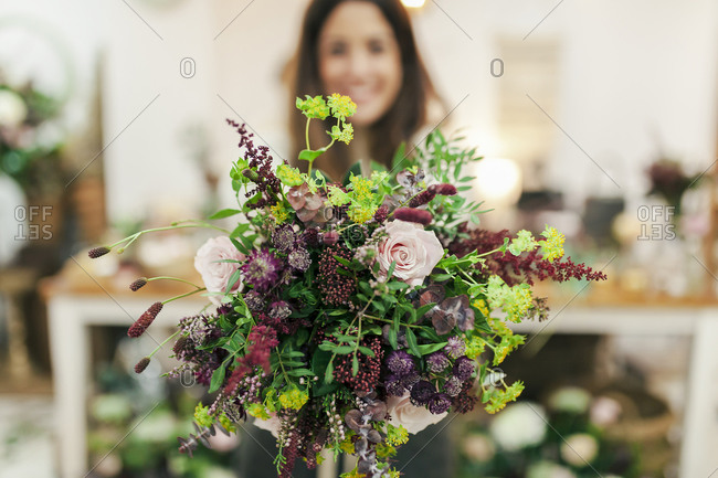 Woman holding bunch of flowers while standing at flower shop