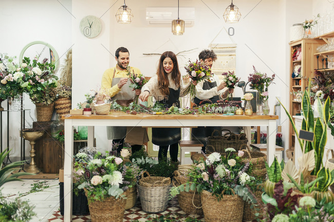 Florist team arranging flowers and plant while standing at flower shop