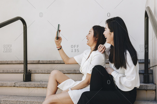 Coworkers taking selfie while sitting on staircase