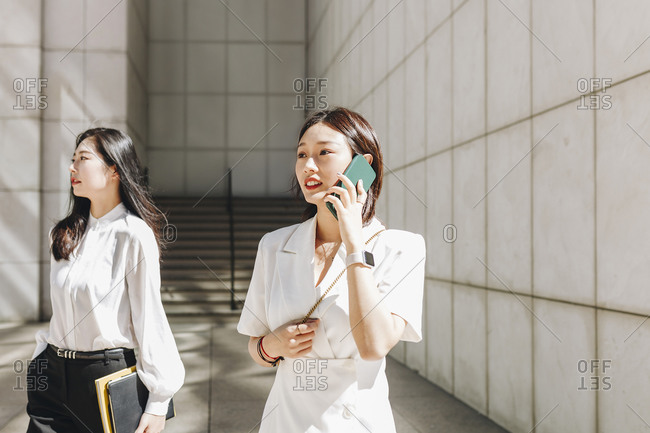 Coworker looking away while businesswoman talking on phone in city during sunny day