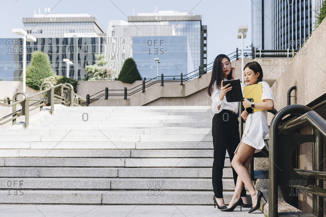 Female entrepreneurs standing on staircase against downtown district while using digital tablet