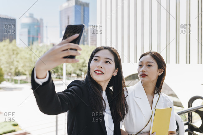 Female colleagues taking selfie on smart phone against financial district in city during sunny day