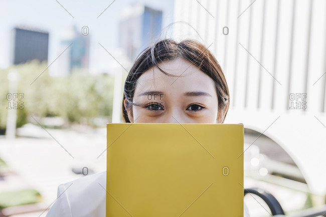 Female entrepreneur covering face with book while standing against financial district