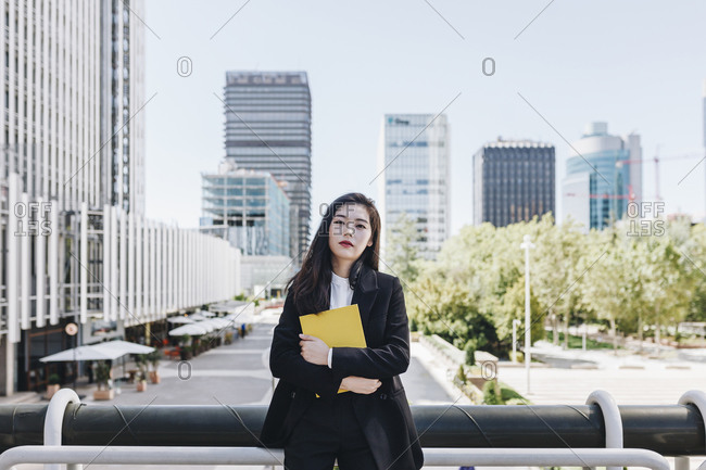 Confident businesswoman with book standing against downtown district in city