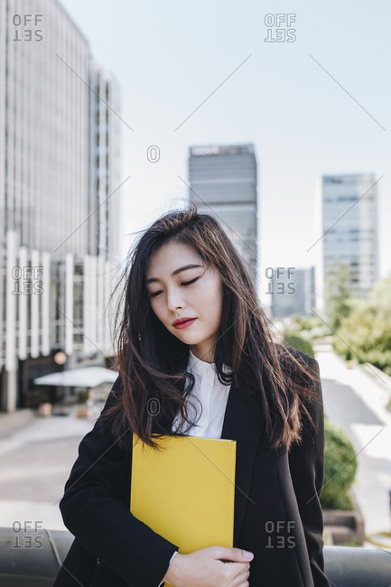 Businesswoman looking down while standing against downtown district
