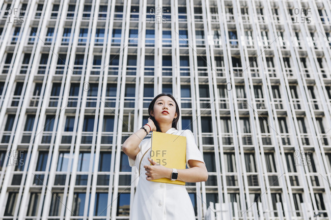 Female entrepreneur holding book while standing against financial district in city