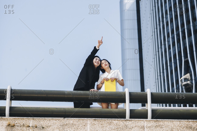 Smiling businesswoman pointing female coworker at downtown district in city against clear sky