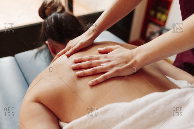 Woman having back massage while lying on stretcher