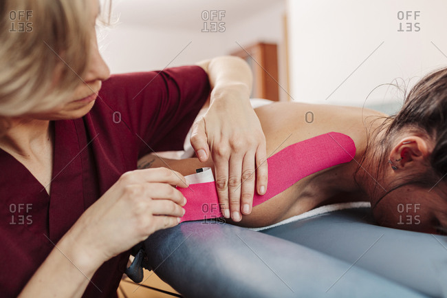 Physiotherapist applying adhesive tape on woman shoulder
