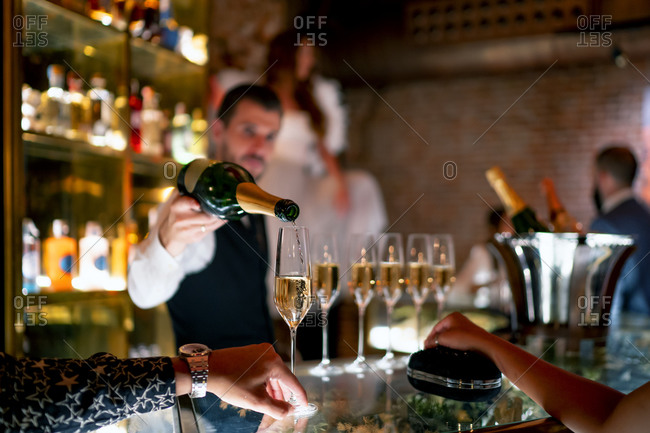 Bartender serving drink to man and woman at bar counter in pub