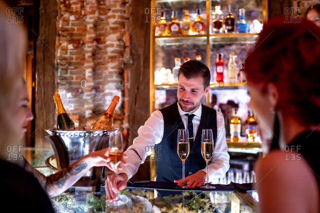 Bartender serving drink to women at bar counter in pub