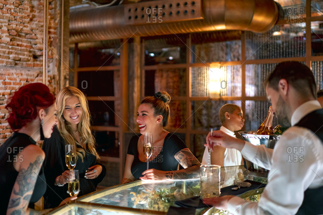 Smiling friends talking while sitting at bar counter in pub