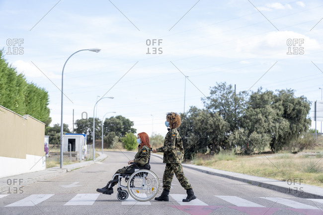 Female military officer pushing army soldier sitting on wheelchair