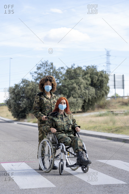 Female army soldier helping military officer sitting on wheelchair while wearing protective face mask