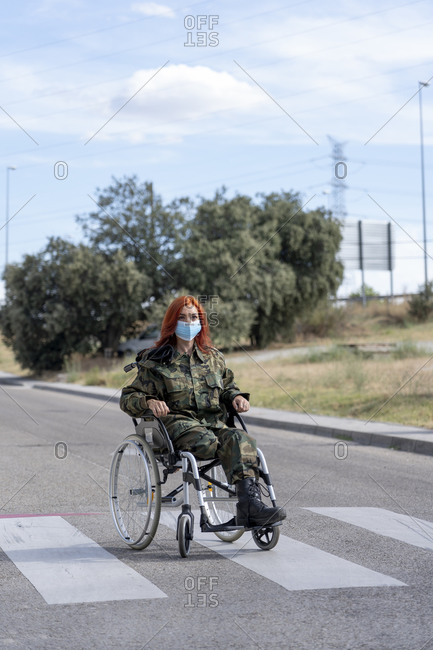Army soldier sitting on wheelchair while wearing protective face mask