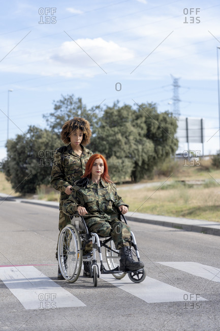 Army soldier helping disabled military officer on wheelchair while standing on street