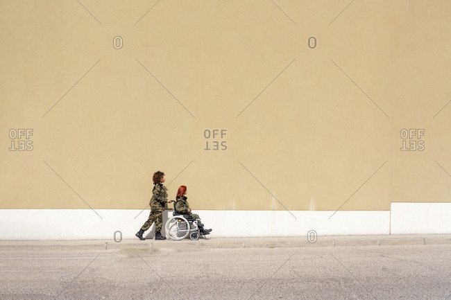 Female military office pushing wheelchair of army soldier while walking against wall on footpath