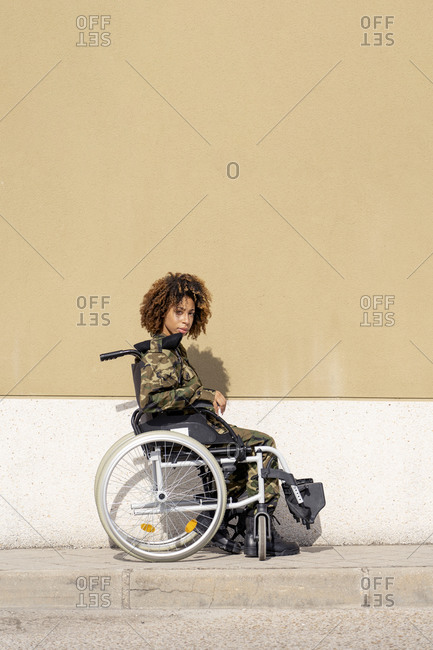 Female military officer sitting on wheelchair against wall