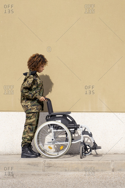 Female army soldier looking at empty wheelchair on footpath against wall