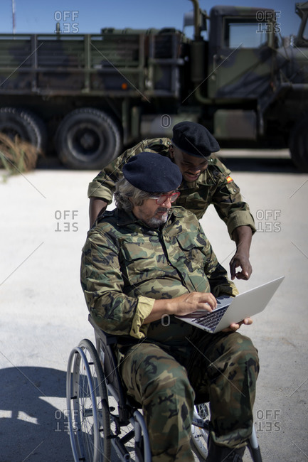 Disabled military officer working on laptop with coworker during sunny day