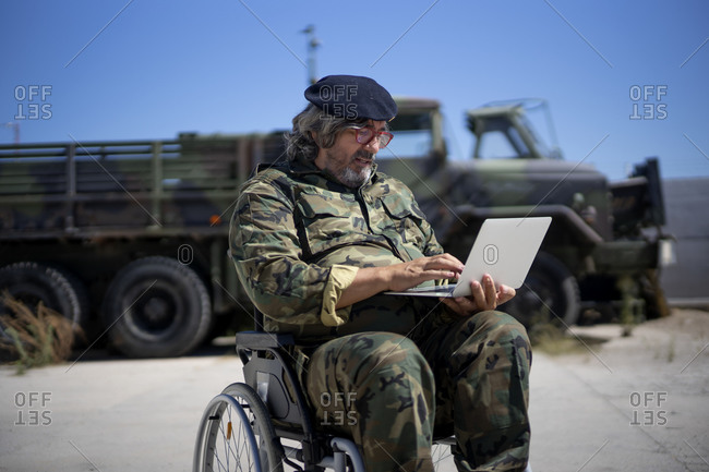 Army soldier using laptop while sitting on wheelchair against military truck during sunny day