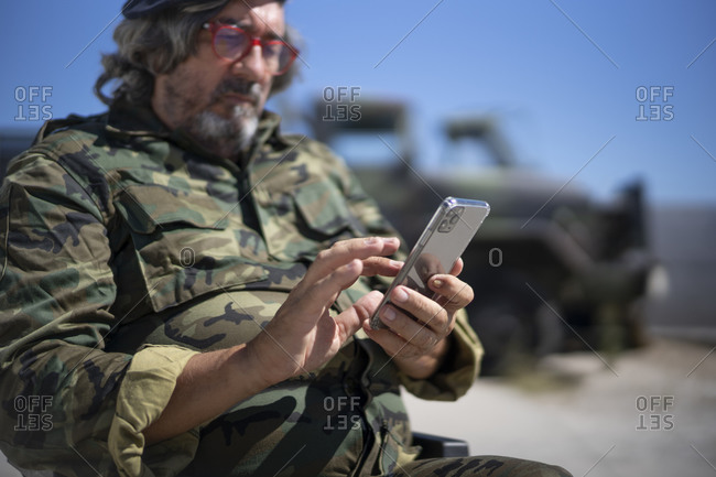 Military officer text messaging on smart phone while sitting on wheelchair during sunny day