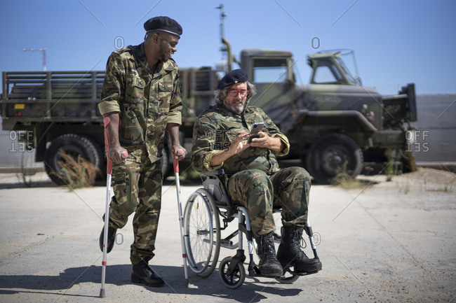 Injured army soldier holding crutches while standing with disabled colleague on wheelchair looking at smart phone during sunny day