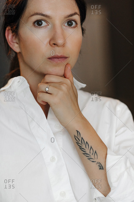 Close-up portrait of confident woman with hand on chin in cafe