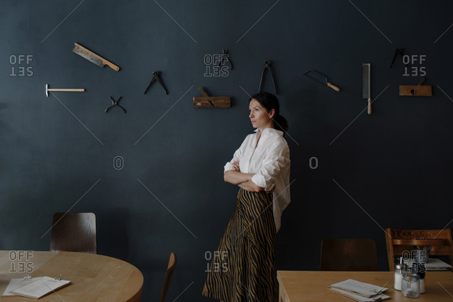 Thoughtful female owner with arms crossed standing by work tool hanging on wall in cafe