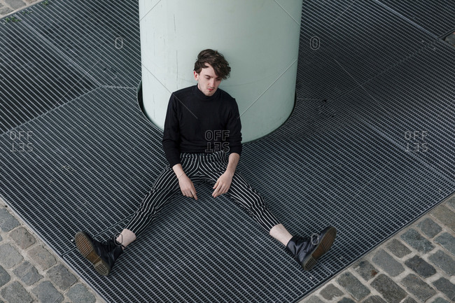 Depressed thoughtful man sitting by column on footpath in city