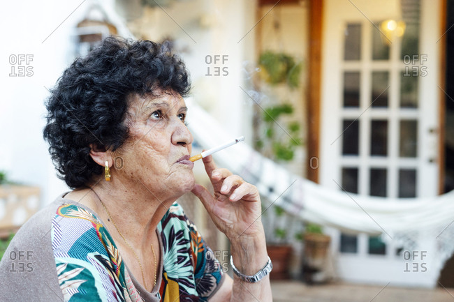 Close-up of senior woman smoking cigarette while sitting outside house in yard