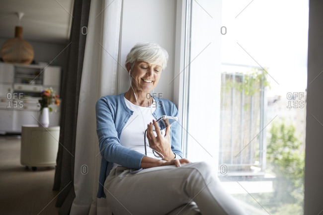 Active senior woman listening to music on smart phone while sitting at home