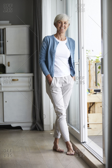 Senior woman standing with hands in pockets at home