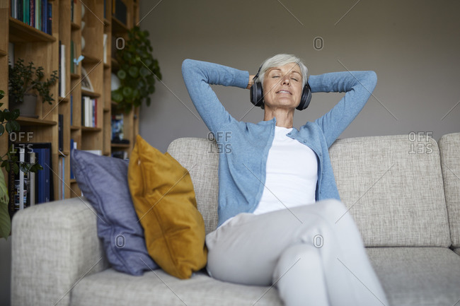 Woman with hands behind head listening to music through headphones at home
