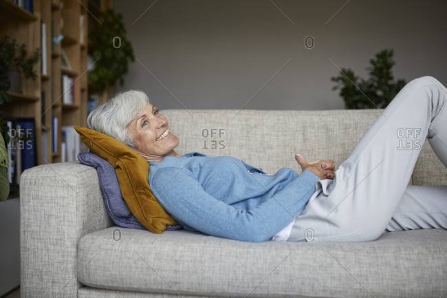 Smiling senior woman lying down on sofa at home