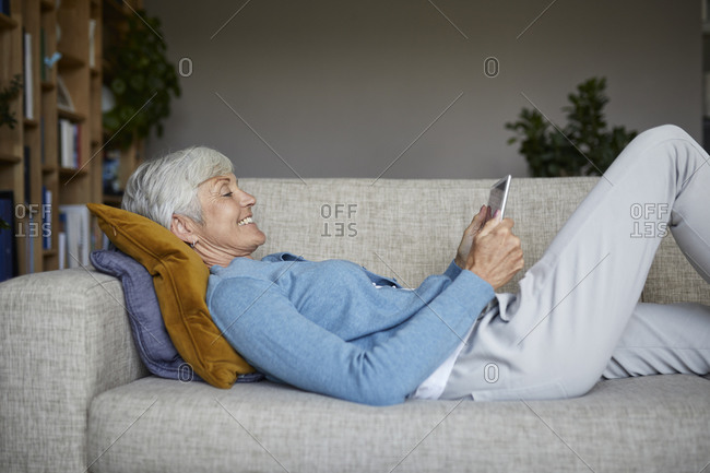 Smiling woman using digital tablet while lying down on sofa at home