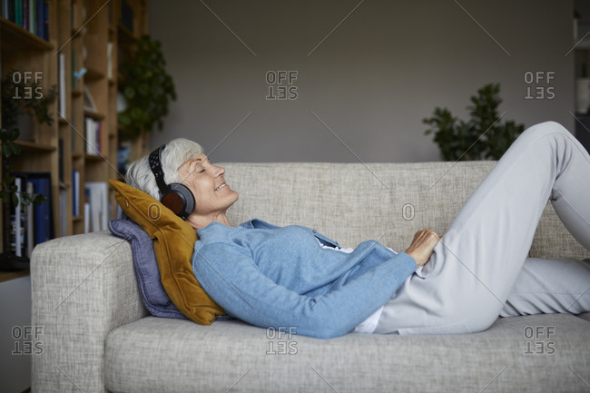 Senior woman listening to music while lying down on sofa at home