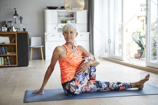 Active senior woman doing yoga sitting on exercise mat at home