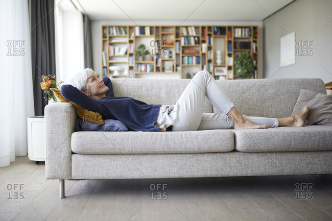 Senior woman with hands behind head lying down on sofa at home