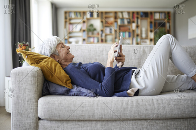 Senior woman text messaging on digital tablet while lying down on sofa at home